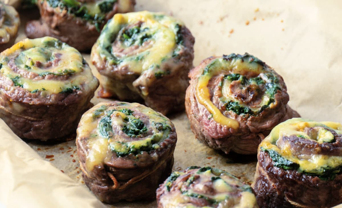 Individual flank steak pinwheels with spinach and havarti cheese.