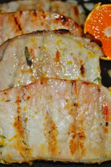 Boneless center cut pork chops marinated in a brine of water, sugar, salt, oranges and fresh thyme; then grilled are super juicy and delicious.