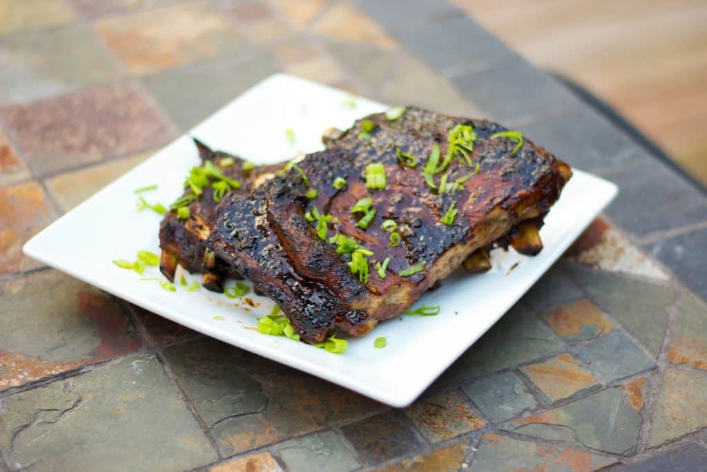 Pork spareribs slowly simmered until they're fall-off-the-bone tender; then brushed with an Asian Marinade and grilled to perfection.