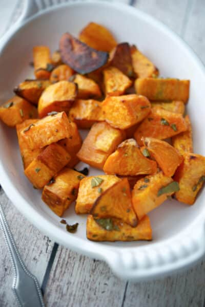 Roasted Sweet Potatoes with Sage in a white baking dish