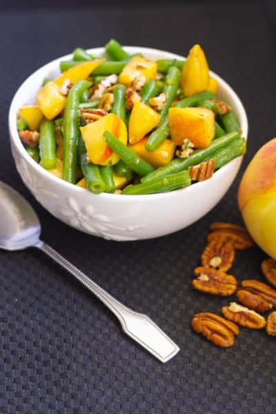 Fresh green beans and sliced peaches tossed with chopped pecans in a maple vinagrette is a delightfully flavorful Autumnal salad.
