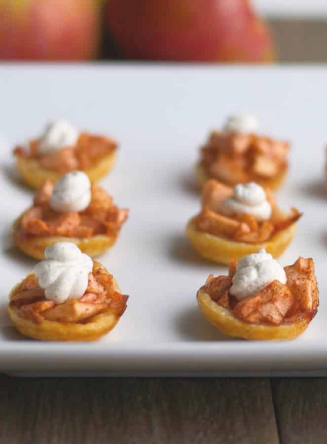 Enjoy one of your favorite holiday desserts by turning them into smaller portions like these Spiked Mini Apple Tarts with Cinnamon Whipped Cream.