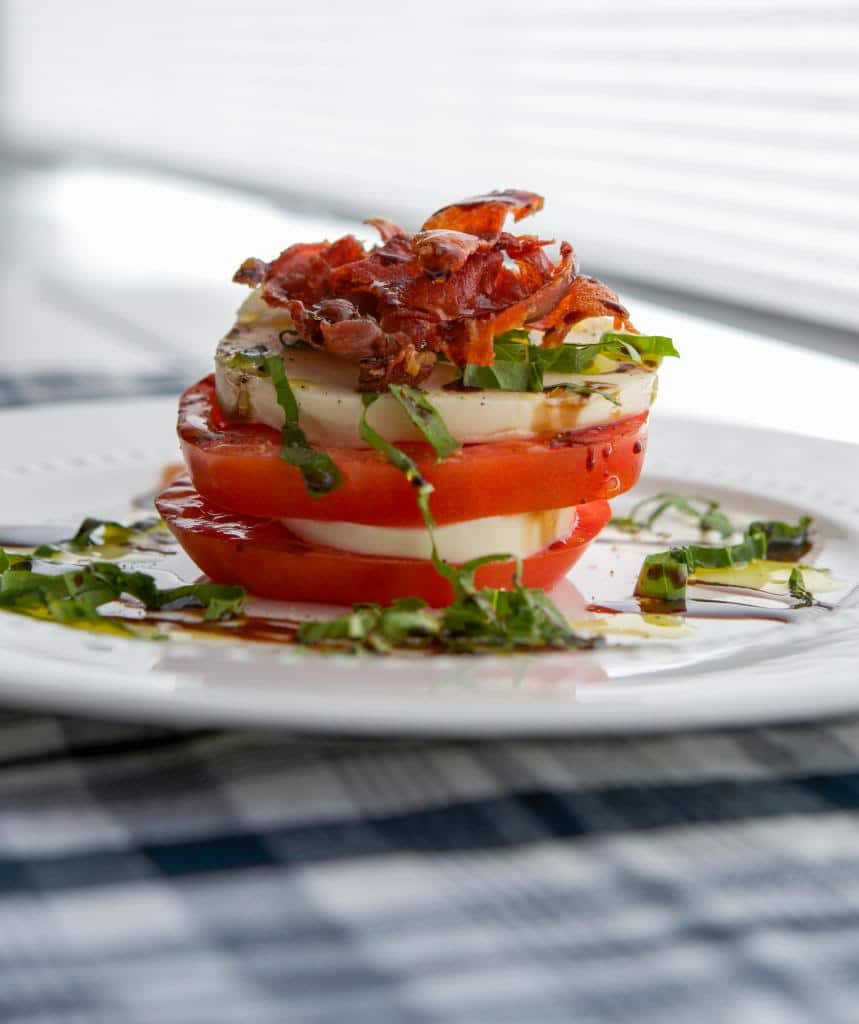 Caprese Stacks made with fresh mozzarella, Heirloom tomatoes and Italian prosciutto then topped with aged balsamic vinegar.