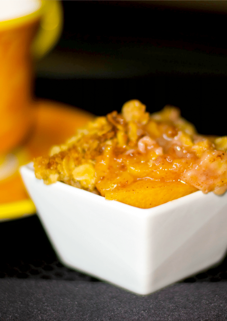 Peach Crisp made with fresh Summer peaches topped with an oatmeal streusel topping; then baked until hot and bubbly.