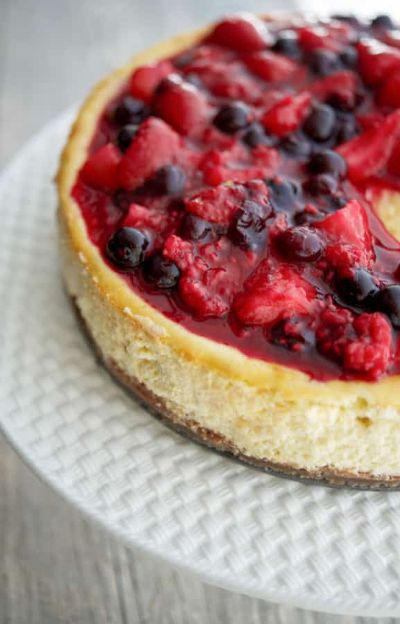 This Vanilla Bean Cheesecake made with cream cheese, Madagascar vanilla extract, vanilla beans, eggs, and sugar; then topped with a compote of fresh raspberries, strawberries and blueberries.