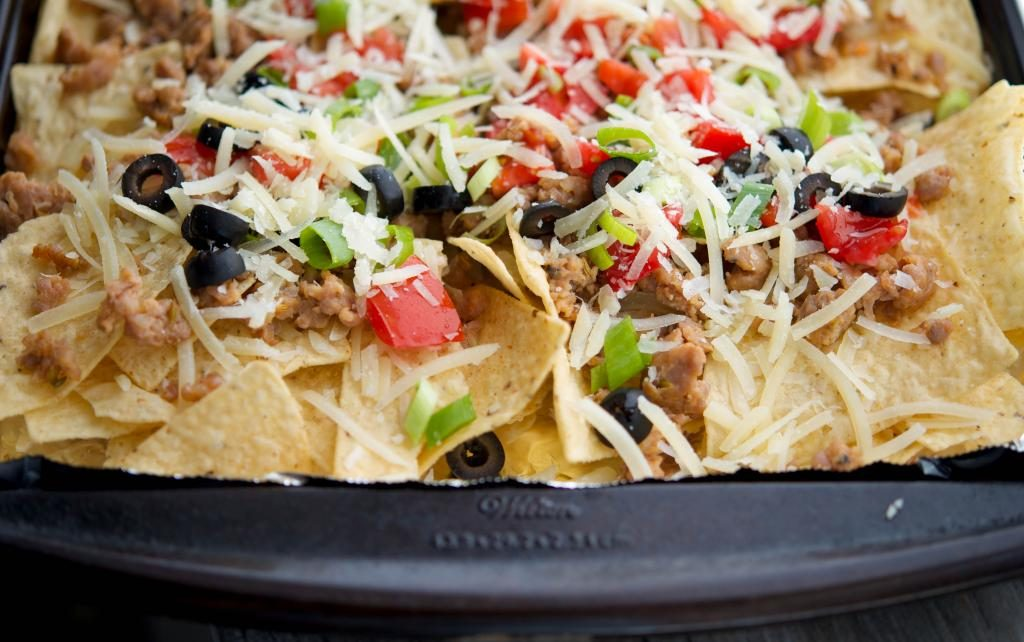 Italian Nachos made with ground pork sausage, black olives, tomatoes, scallions and melted Asiago cheese make the perfect game day snack. #appetizer #nachos #gameday