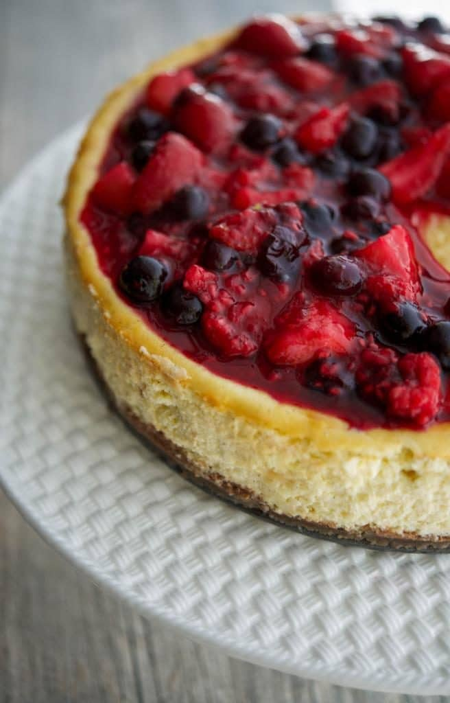 This Vanilla Bean Cheesecakemade with cream cheese, Madagascar vanilla extract, vanilla beans, eggs, and sugar; then topped with a compote of fresh raspberries, strawberries and blueberries.