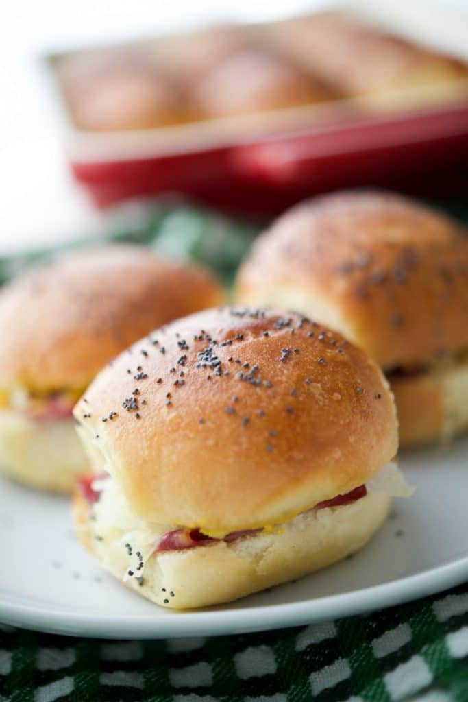 These Cheesy Irish Sliders made with corned beef, Dubliner Irish cheese, sauerkraut & Irish mustard on potato slider rolls are a must have! ohsweetbasil.com