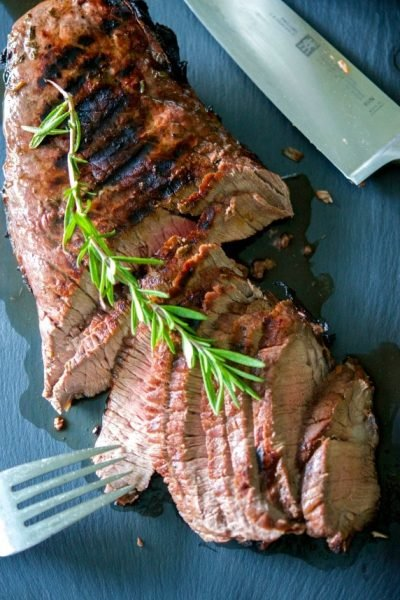 Beef London broil marinated in red wine, garlic, rosemary, balsamic vinegar and light olive oil; then grilled to your liking.