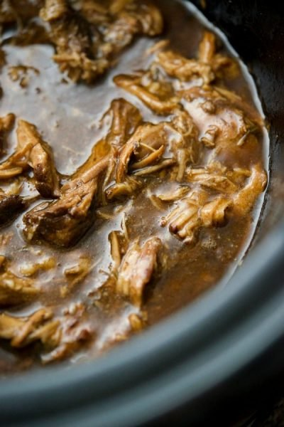 Pork shoulder cooked slowly in your crock pot with fresh garlic, rosemary, beef broth and balsamic glaze. Serve on top of egg noodles or make a sandwich.