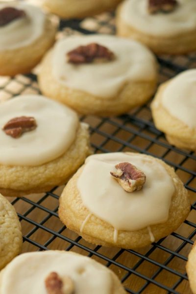 Soft and chewy in texture, these Maple Sugar Cookies coated with a maple syrup glaze and pecans are a must have Fall treat.
