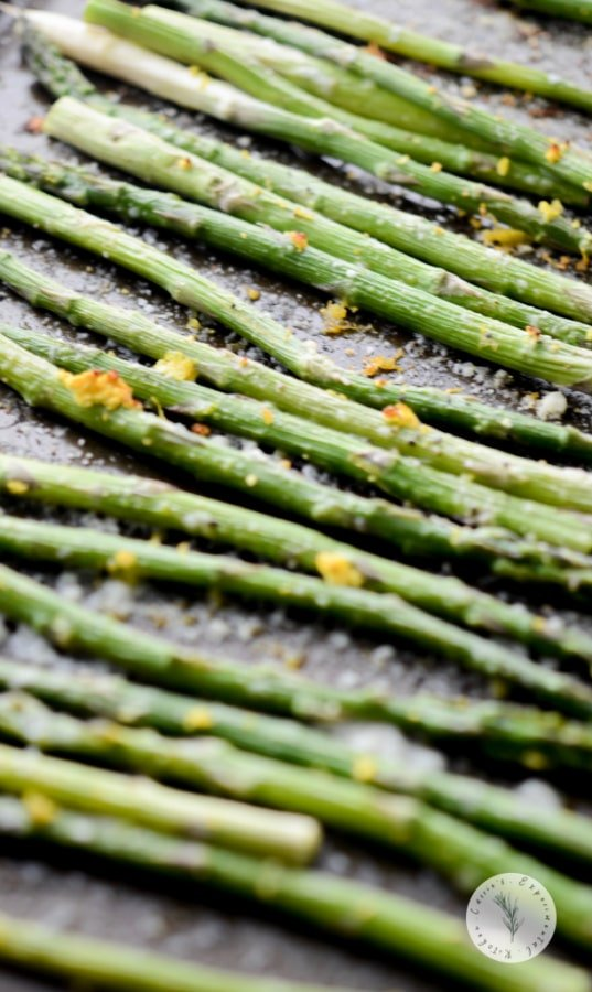 Fresh bundles of asparagus tossed with lemon zest, grated Parmesan cheese, Extra Virgin Olive Oil; then briefly roasted in the oven until al dente.
