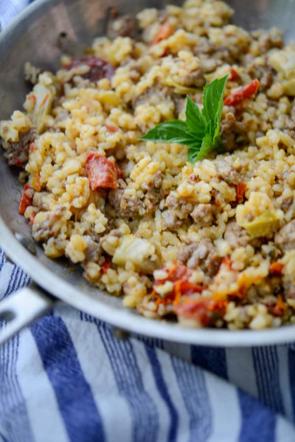 This risotto made with Italian sausage, artichoke hearts and sun dried tomatoes is deliciously flavorful and can be made in one skillet.