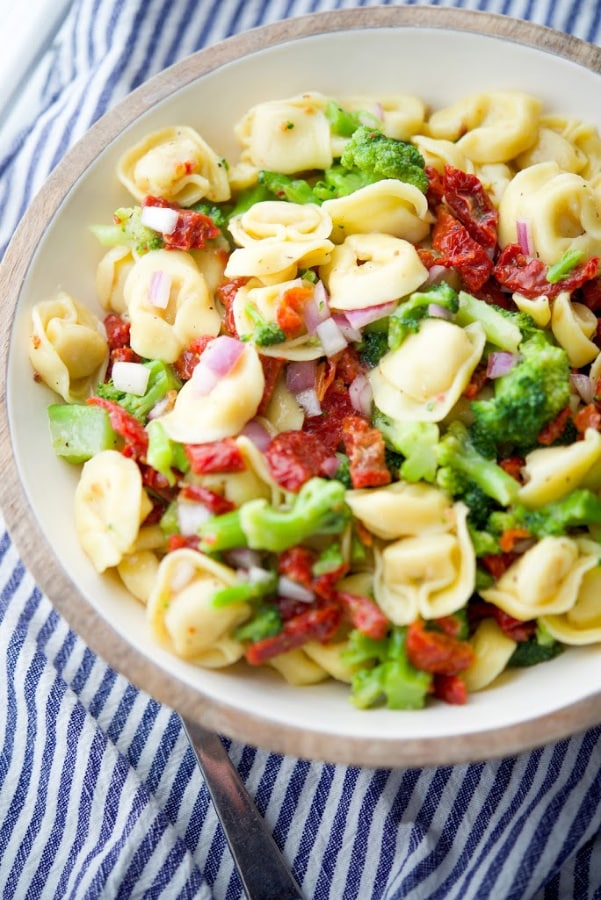 Cheese tortellini combined with fresh sun dried tomatoes, broccoli florets, and onions in a zesty Italian vinaigrette dressing is a hearty cold pasta salad that's great for get togethers.