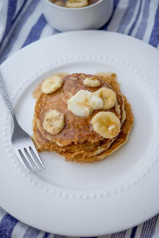 Pancakes made with rolled oats, flour, milk, eggs and fresh bananas topped with banana maple syrup is a delicious way to start the day.