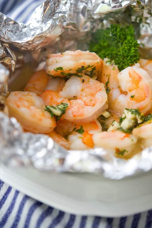 Shrimp Scampi made with garlic, white wine, butter and lemon juice grilled in foil packs is a tasty way to enjoy a meal outdoors with little cleanup.