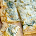 Spinach & Artichoke Flatbread made with spinach, artichoke hearts and a lemony, cheese sauce is perfect for pizza night or game day snacking.
