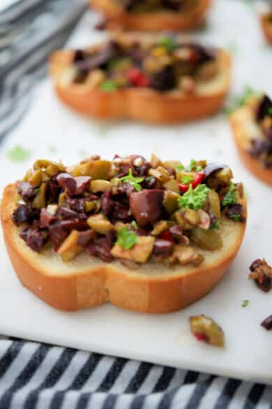 Olive Rosemary Tapenade made with a variety of olives like Kalamata, Pimento, Garlic and Sicilian on toasted bread rounds make a tasty, last minute appetizer.