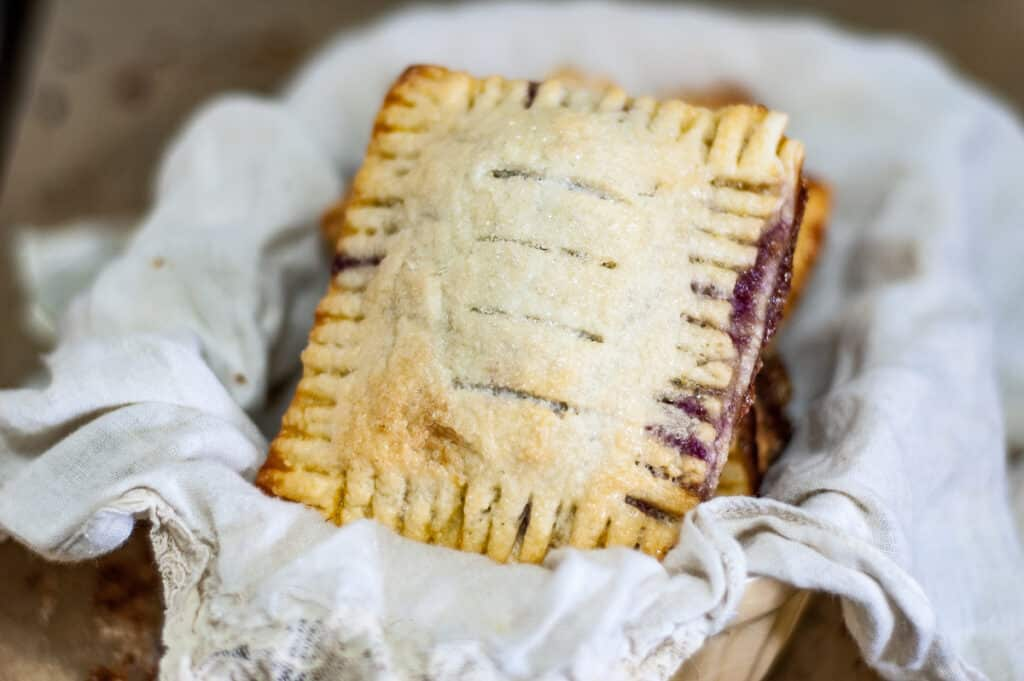 Mixed Berry Hand Pies in a basket with white napkin