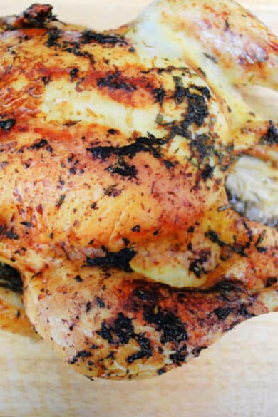 Roasted whole chicken with grapefruit and herbs on a cutting board.