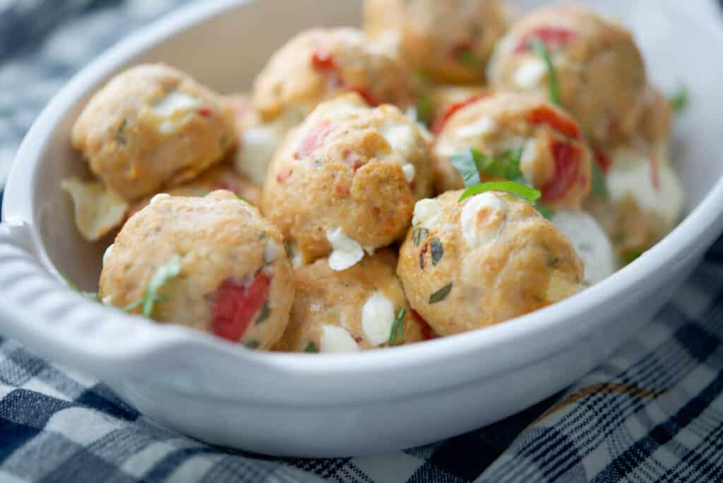 Baked Caprese Chicken Meatballs in a white dish