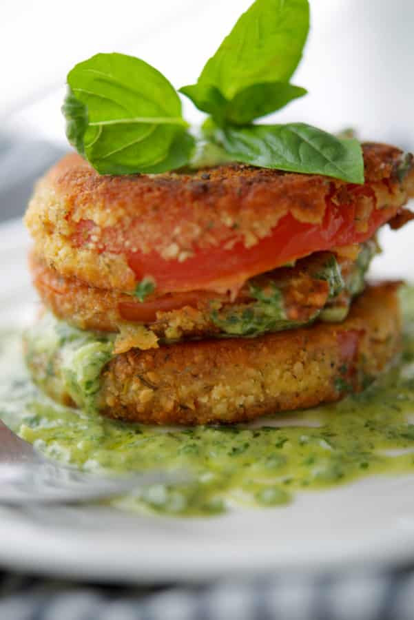 Fried tomatoes with pesto crema on a white plate