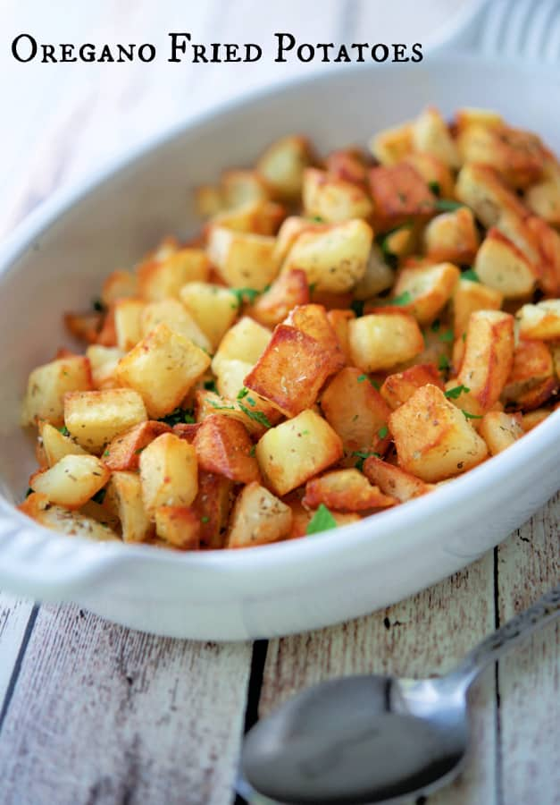 Oregano Fried Potatoes in a white dish with spoon